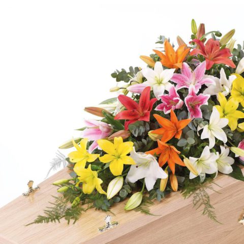 A blanket of Oriental lilies is beautifully complemented by an array of luxurious deep green leaves to create this simple but striking casket spray.