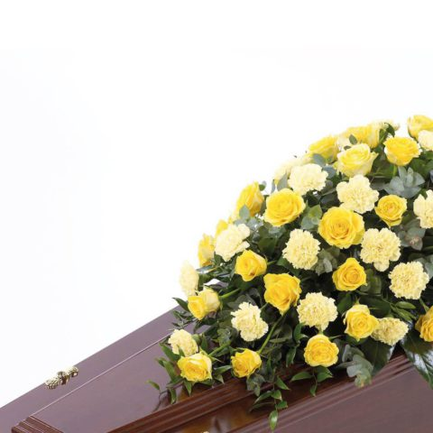 Large-headed roses combine with carnations and luxurious foliages to create this traditional casket spray.