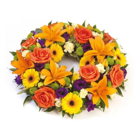 Lilies and large-headed roses are nestled amongst freesias and lisianthus along with eryngium and foliage in this circular wreath.