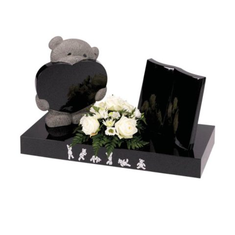A delicately carved teddy with heart and free standing book.
